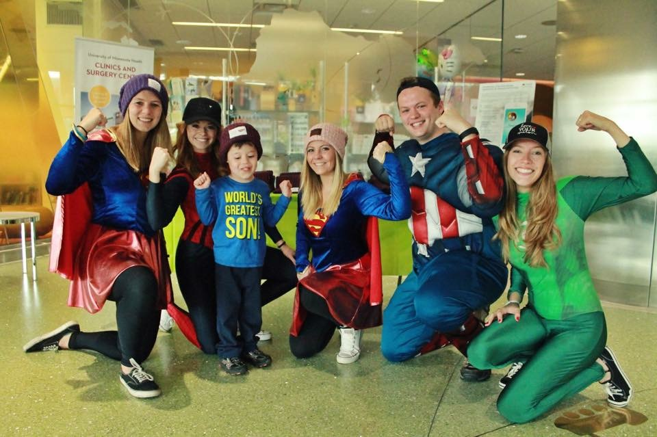 7b7eca27d7588 St. Thomas Love Your Melon campus crew members pose wearing superhero  costumes while visiting children