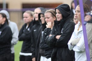 <p>Tommie players stand out in the rain to cheer on their teammates near the end of the game. (Miles Trump/TommieMedia)</p>