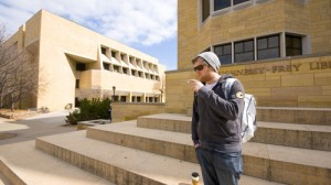 Dustin Hassett smokes a cigarette outside the O'Shaughnessy-Frey Library. (John Kruger/TommieMedia)