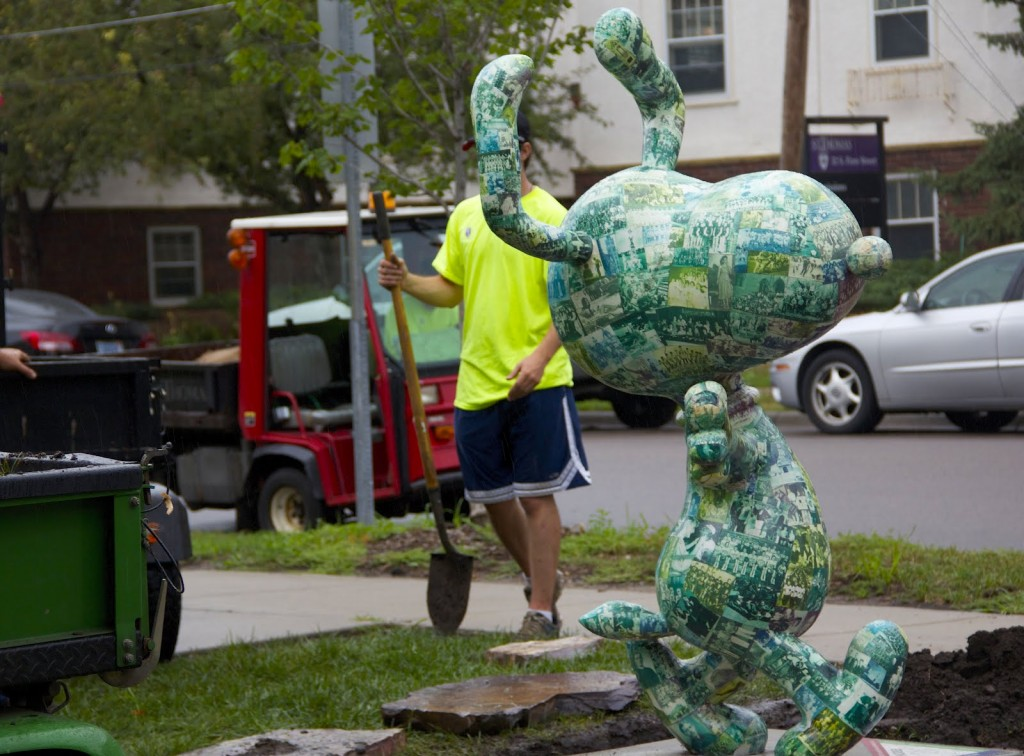 <p>St. Thomas grounds workers landscape around the donated Snoopy statue on July 24, 2012. The St. Thomas alumnus, who wants to remain anonymous, worked with the university when he chose from the archives to decorate Snoopy's surface. (Hannah Anderson/TommieMedia)</p>