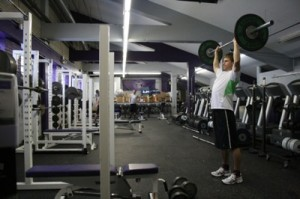 <p>Sophomore Kelvin Kosbab finishes a lift in the temporary weight room facility located under the bleachers of O'Shaughnessy Stadium. (Michael Ewen/TommieMedia)</p>